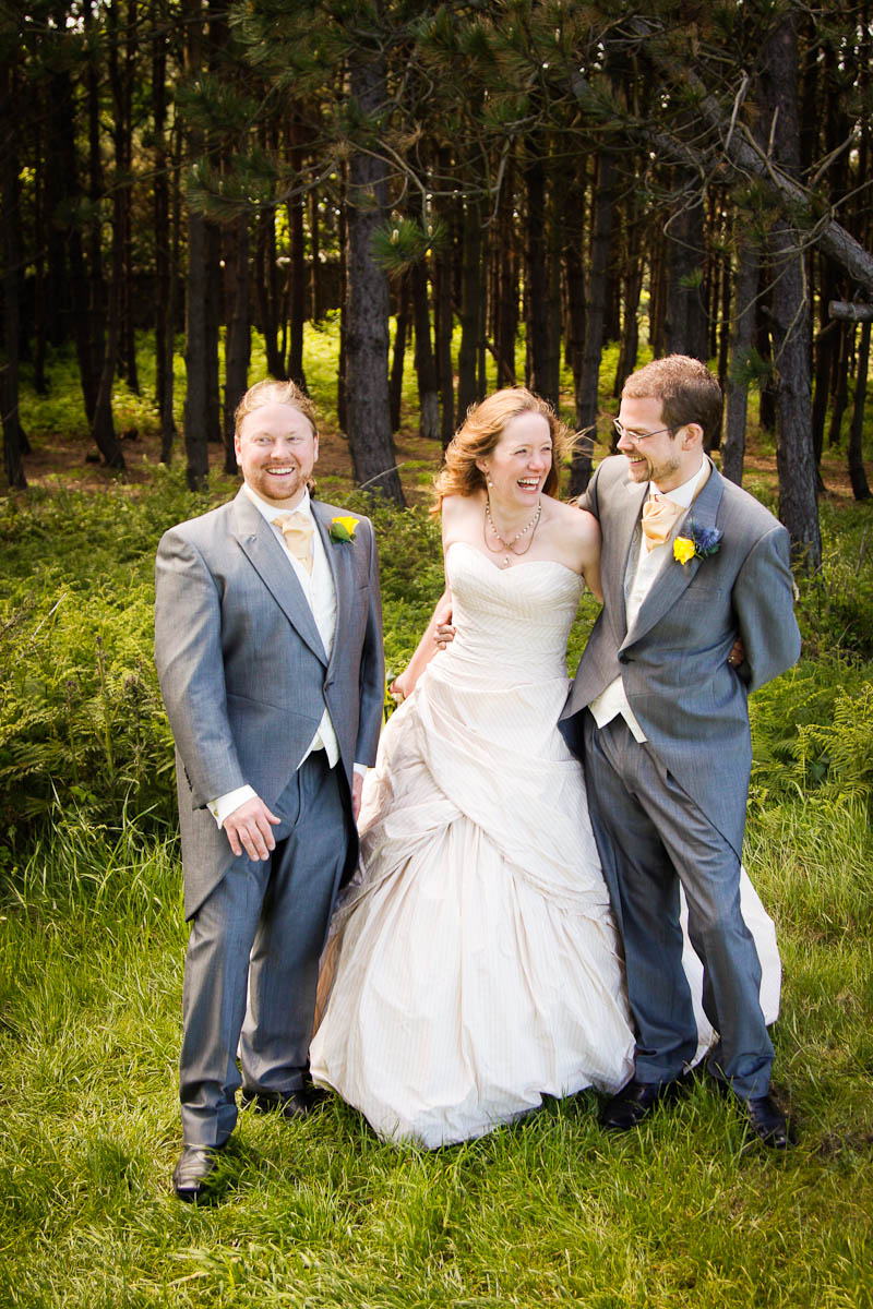 bride and groom with best man at outdoor wedding on windy day