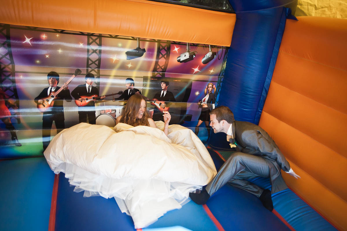 bride and groom on bouncy castle at wedding