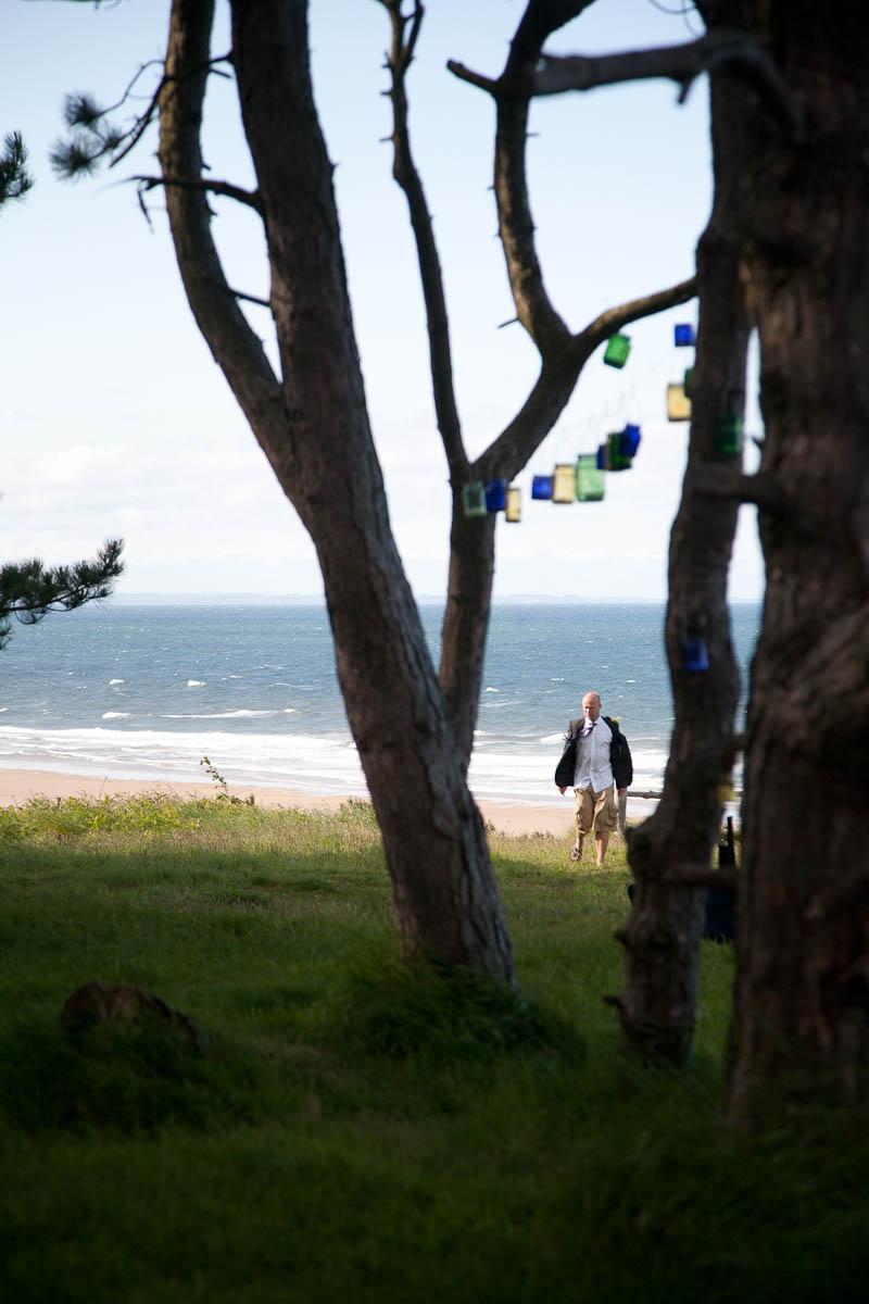tea lights in jam jars hung beteen tress at beach weddingt