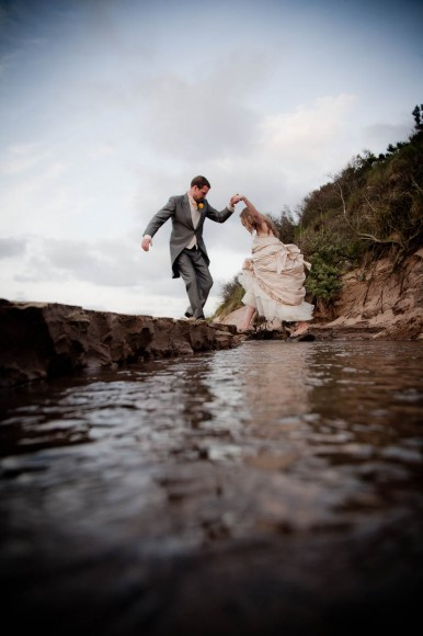 groom helps bride over stream at beach wedding