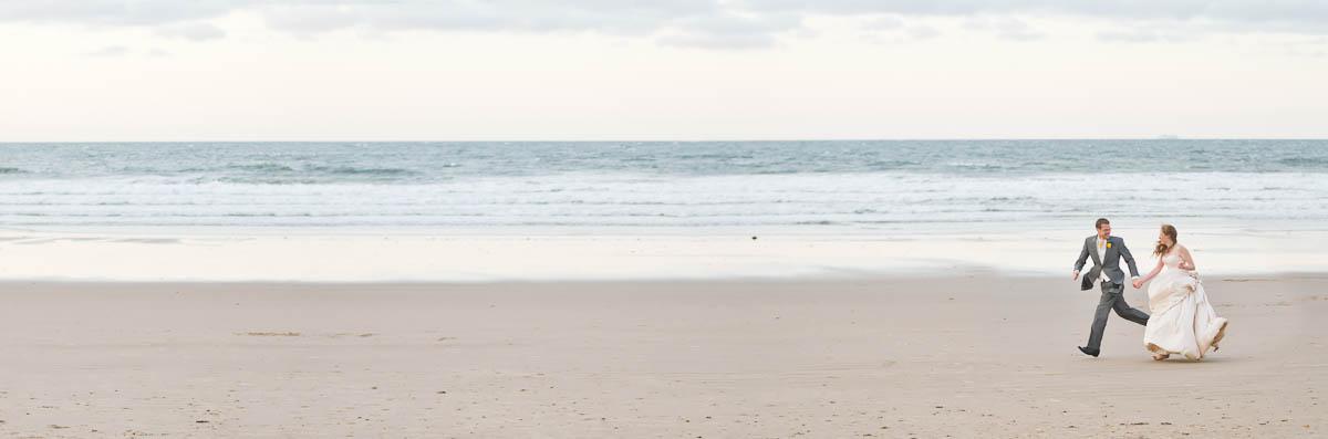 bride and groom run along beach