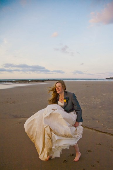 bride in groom's jacket almost blow away on beach at wedding on windy day