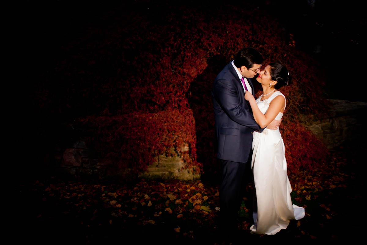 bride and groom kiss outside amidst leaves in dark
