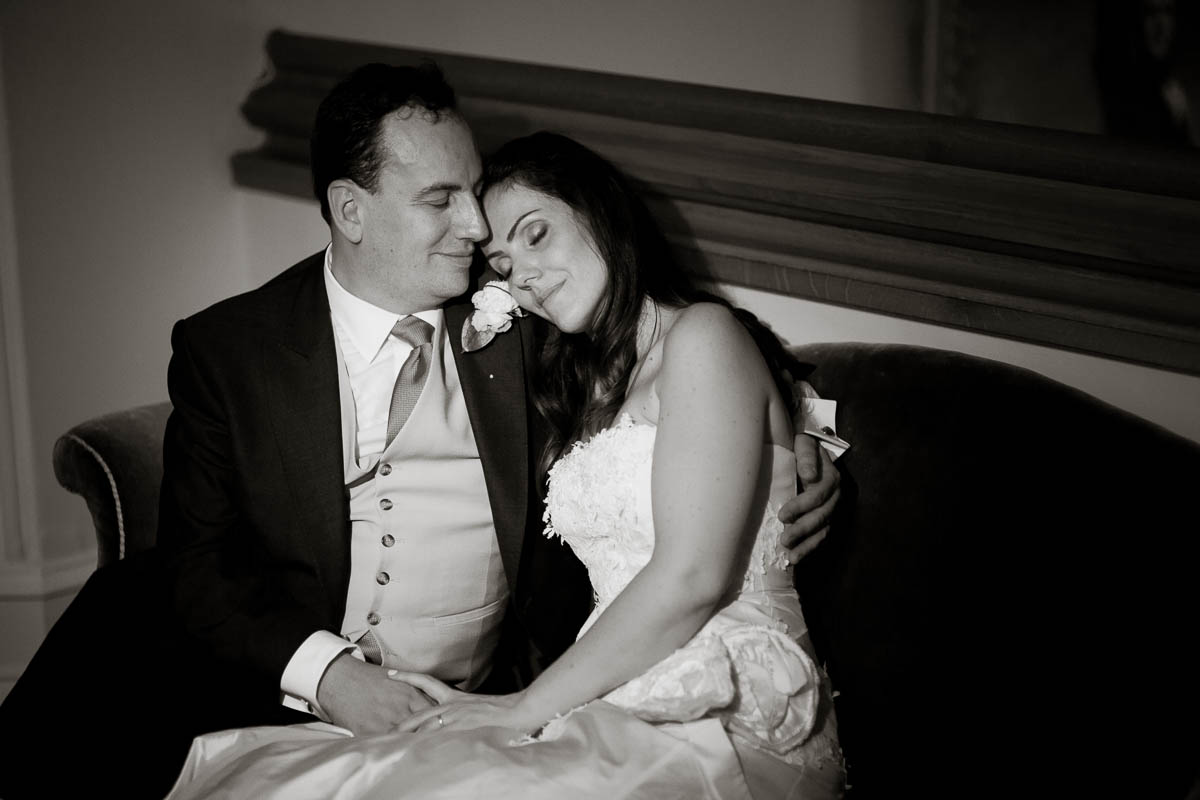 newly wed couple snuggle at wedding at drummuir castle black and white