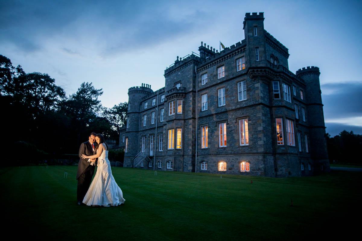 bride and groom outside drummuir castle at dusk
