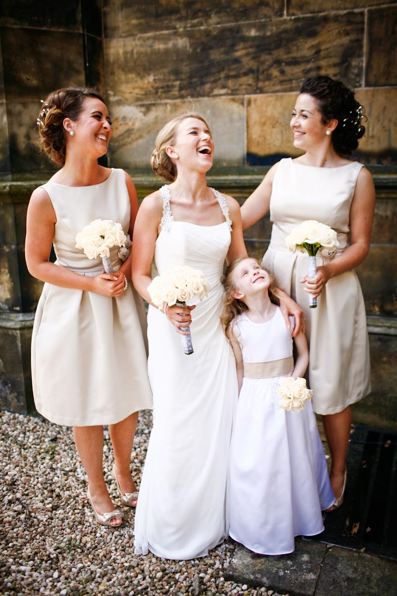 bride with bridesmaids and flower girl laughing