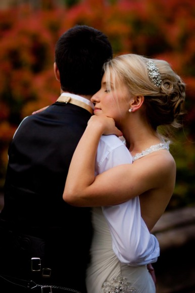 bride and groom embrace outside