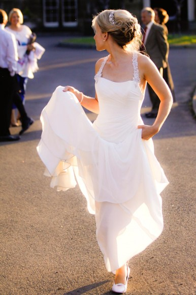 bride holds up dress from ground