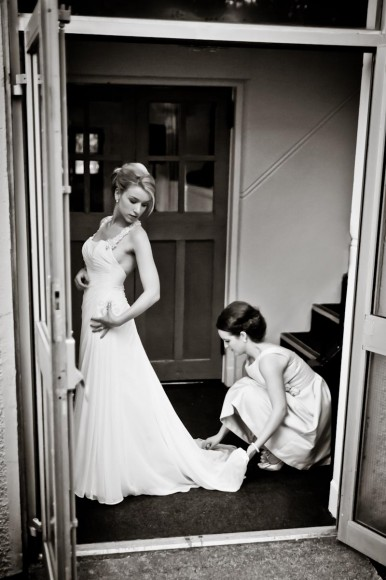 bridesmaid sorts bride's train and helps her get ready