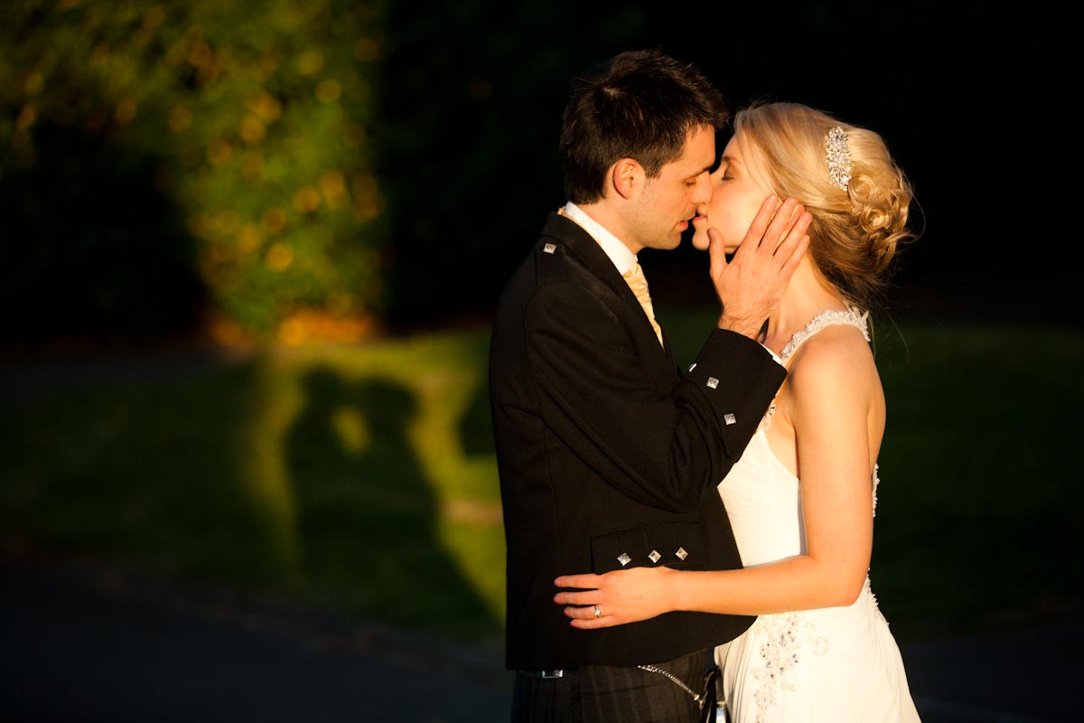 bride and groom kiss outside in sunset