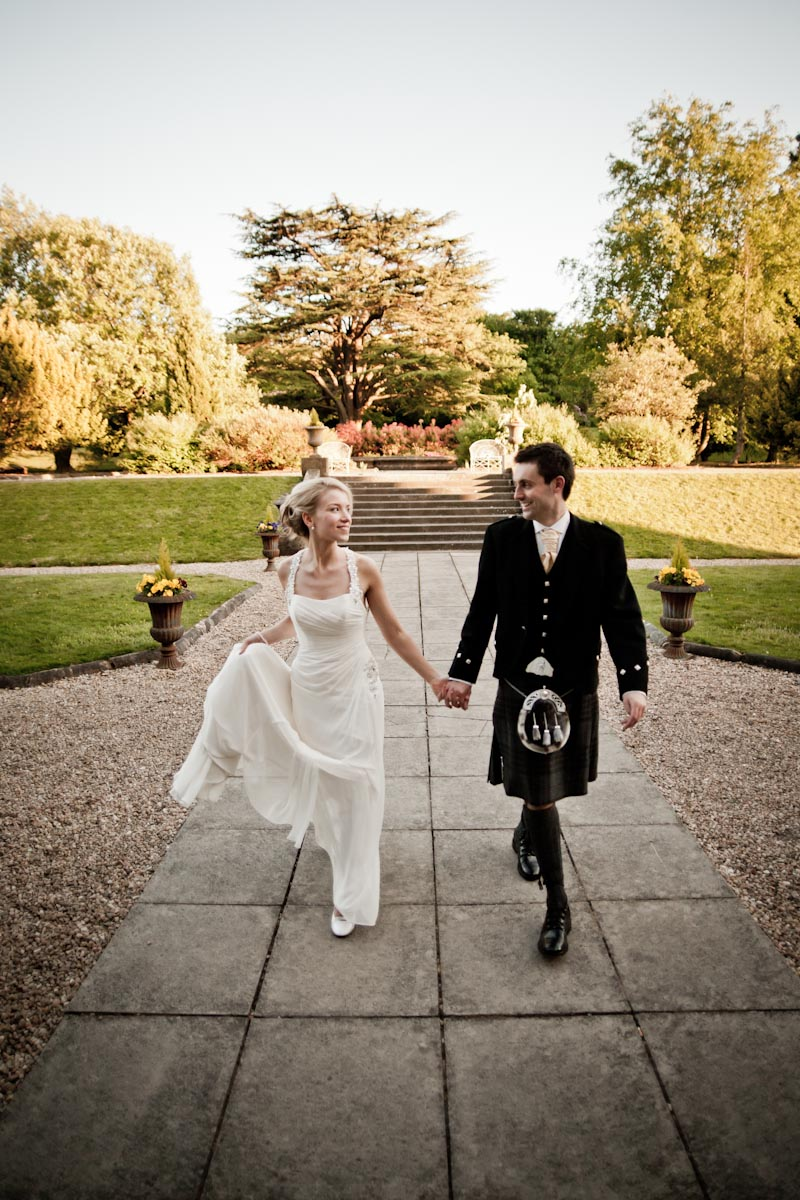 bride and groom walk in grounds of mar hall glasgow