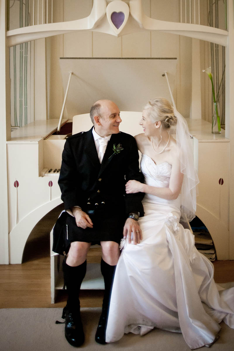 bride and groom on piano stool at house for an art lover in glasgow