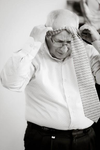 man putting on pre-tied tie