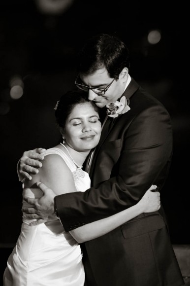 bride and groom embrace in black and white.