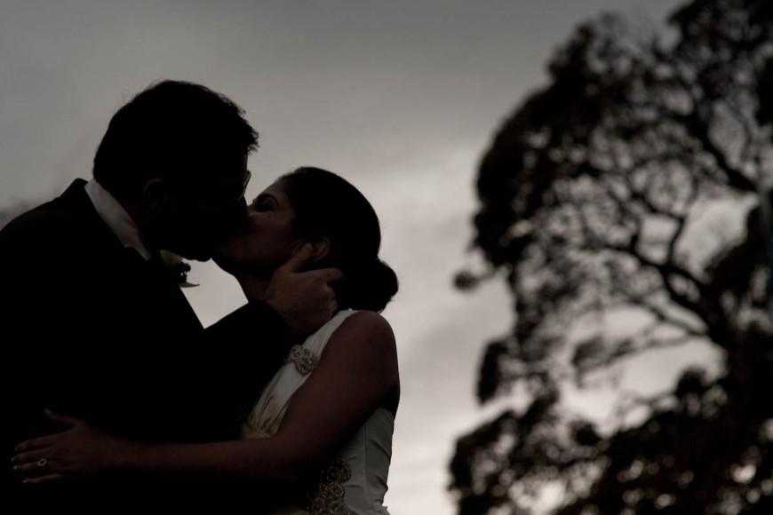 bride and groom kiss outside