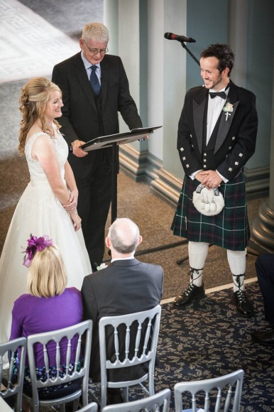 bride and groom smile at front at wedding in signet library edinburgh