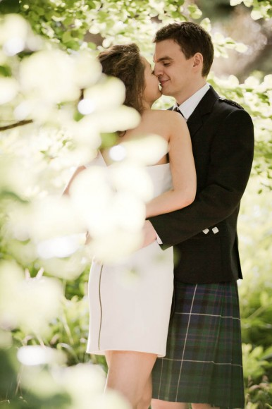bride and groom embrace with tree
