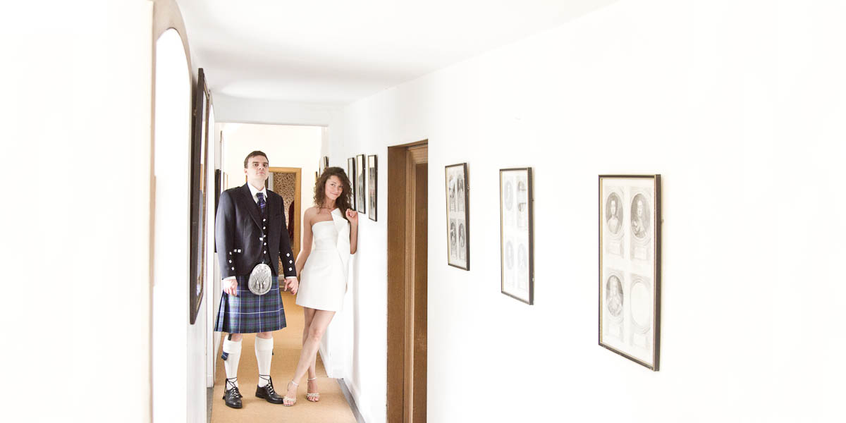 bride ad groom in hallway with pictures