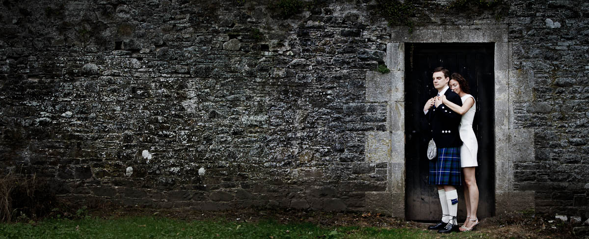 bride and groom outside with stone wall