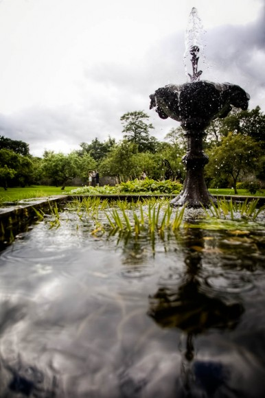 bride and groom by fountain at traquair house