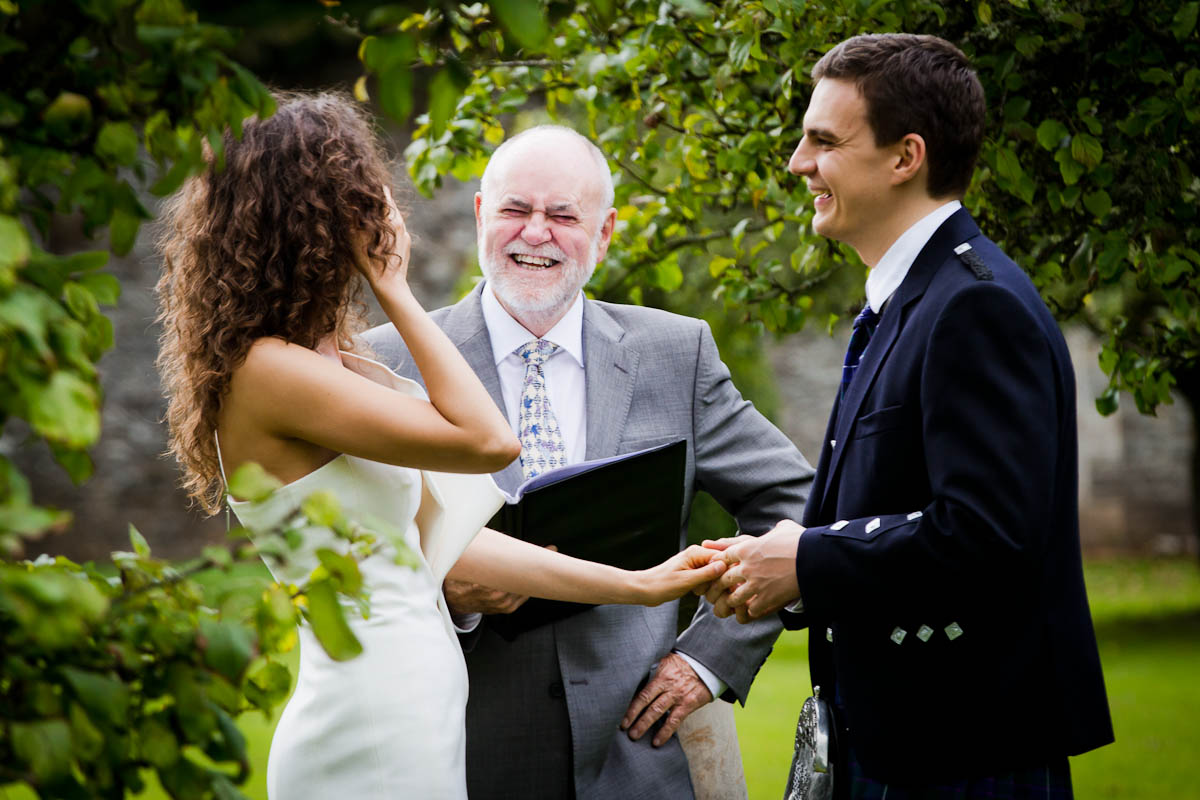 bride and groom with celebrant in garden of traquair house