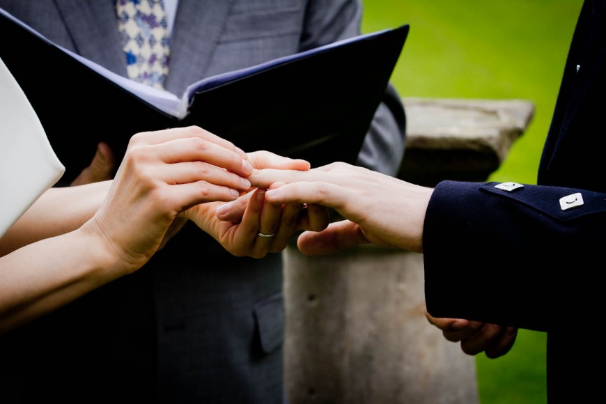 bride and groom exchange rings outside