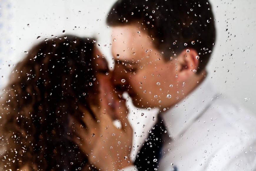bride and groom kiss behind raindrops on window