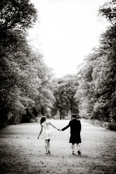 bride and groom walking through avenue of trees