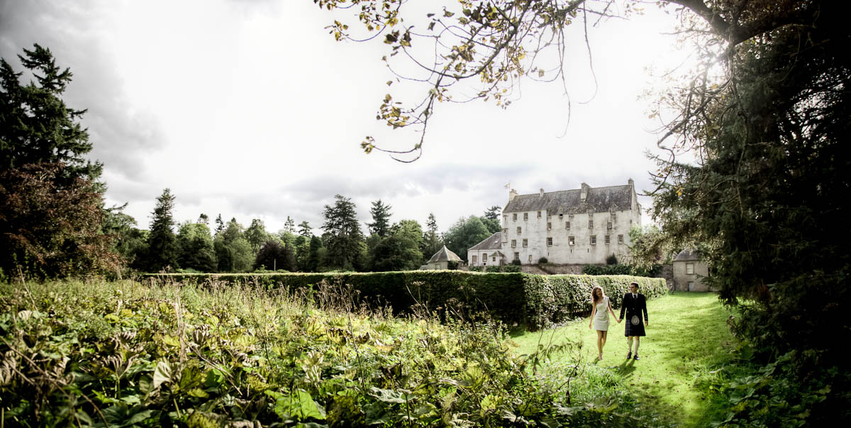 bride and groom walk in grounds of traquair house