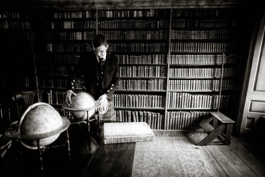 groom in library with globe