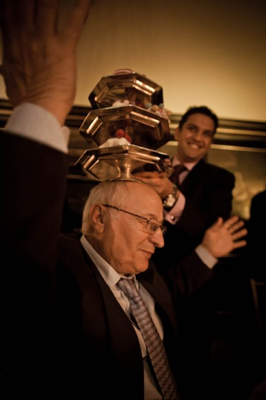 old man balances trays on head at wedding